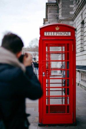 Photo pour Jeune touriste prenant une photo d'une cabine téléphonique rouge pendant la journée à Londres, Royaume-Uni . - image libre de droit