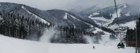 Photo pour Vue panoramique de la station de ski de Bukovel depuis les remontées mécaniques, la neige, les montagnes et les arbres en arrière-plan. Bukovel est l'une des stations de sports d'hiver les plus populaires en Ukraine . - image libre de droit