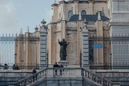 Photo pour Madrid, Espagne - 26 janvier 2020 : Personnes passant devant une statue à l'extérieur de la cathédrale d'Amudena (Catedral de la Almudena), église catholique et siège de l'archidiocèse catholique romain de Madrid, Espagne. - image libre de droit