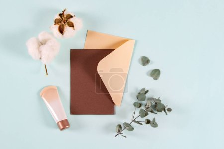 Photo for Blank paper envelopes, letters for invitation, mail with eucalyptus leaves, cream jar and cotton flowers on blue background, mockup, flat lay, top view. Natural organic beauty product - Royalty Free Image