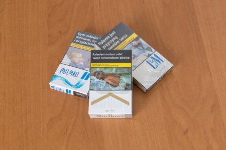 Deblin, Poland - April 18, 2018: L&M link blue, Pall Mall longs and Marlboro gold cigarettes pack on wooden table.