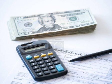 Photo pour Photo en gros plan d'une copie papier d'une déclaration de revenus des particuliers avec calculatrice noire et billets de 20 dollars empilés représentant les réductions d'impôt fédérales et les économies des États-Unis cette année . - image libre de droit