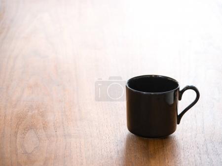 Photo pour Photo de fond rapprochée d'une seule tasse ou tasse à thé ou à café vide en porcelaine noire ou en céramique isolée sur une table en grain de bois foncé et des poignées courbes en demi-cœur . - image libre de droit