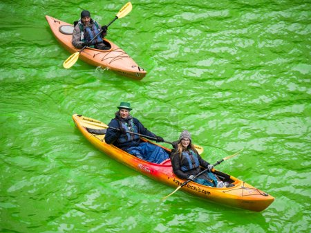 Chicago, IL - March 17th 2018: Kayaks make their way down the freshly dyed green river in downtown Chicago during the city's annual St. Patrick's Day celebration.