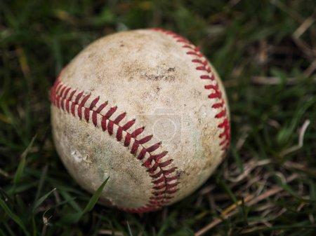 Photo pour Gros plan sport fond image d'un vieux utilisé usé cuir baseball balle pose dans le domaine de l'herbe hors Affichage détails complexes et lacets rouges. - image libre de droit