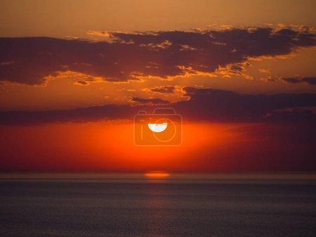 Photo pour Belle photographie du lever du soleil avec des couleurs orange et jaune vif sur les eaux sombres du lac Michigan à Chicago avec des couches de nuages dans le ciel au-dessus . - image libre de droit