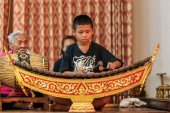 RATCHABURI, THAILAND - MARCH 20, 2016: Unidentified boy playing xylophone on the stage of Wat Khanon, Thailand. Wooden xylophone called ranat is most prominent instrument in classical Thai music.