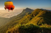 Colorful hot air balloons flying over on Pha Tung mountain in sunrise time, Chiang Rai, Thailand.