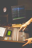sound engineer hands working on digital sound mixer in recording, broadcasting, post production studio.