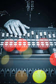 DJ hands working on sound mixer in night club with colourful bokeh