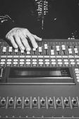 sound engineer hands working on sound mixer in digital music editing studio or live concert, black and white