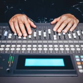 sound engineer hands working on sound mixer in digital music editing studio or live concert