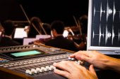 sound engineer hands working on digital sound mixer for symphony orchestra live concert recording