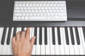 male musician hands playing on piano keys, music computer