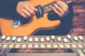 male musician playing electric guitar behind sound mixer in recording studio, focus on fader