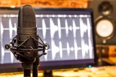 condenser microphone on computer screen showing digital wave & studio monitor speakers background, recording concept