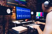 asian male hipster sound engineer working on computer in digital audio & video editing post production studio