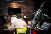 condenser microphone on back of asian male sound engineer working in recording studio background