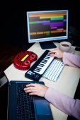 male composer hands using computer, midi keyboard & studio equipment making songs and sound design on desk for post production or music score on film