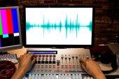 male sound engineer hands control digital sound mixer workstation in tv station editing studio