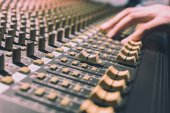 male sound engineer hands working on sound mixer, focus on fader. recording, broadcasting, music production background