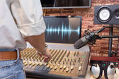 back of male sound engineer working on sound mixer for recording, broadcasting, music production