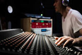 asian male dj, sound engineer, music producer working on sound mixer in recording, broadcasting studio. focus on hands
