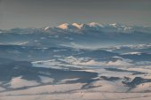 Snowy Little Fatra peaks and forest in mist at sunrise Slovakia
