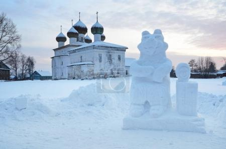 Russia, Arkhangelsk region. Kargopol, Ice sculpture of Masha and bear in front of Annunciation (Blagoveschenskaya) church in the winter evening on New square at sunset