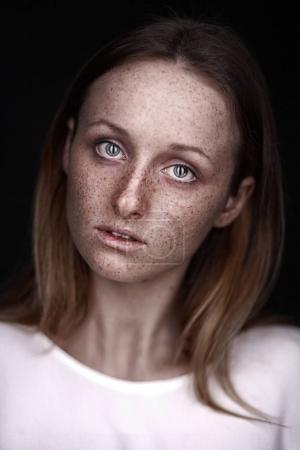 Photo pour Closeup portrait en studio de femme de taches de rousseur rousse portant un t-shirt blanc sans maquillage sur fond noir - image libre de droit