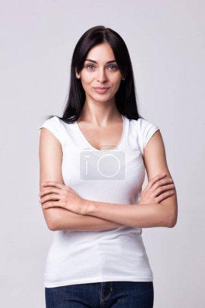 Photo pour Portrait studio de belle femme souriante aux mains croisées - isolée sur fond de studio gris - image libre de droit