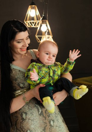 Beautiful young caucasian mother holding her little baby son in her arms in the stylish studio on a background of light bulbs in a modernist style, cuddle her son. minimalism, interior, low key