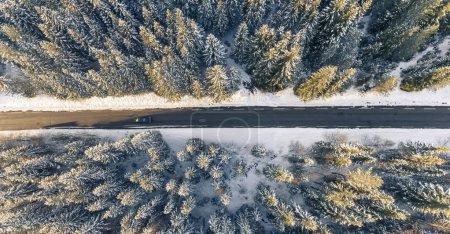 Photo pour Vue aérienne de la voiture noire sur route dans forêt belle hiver - image libre de droit