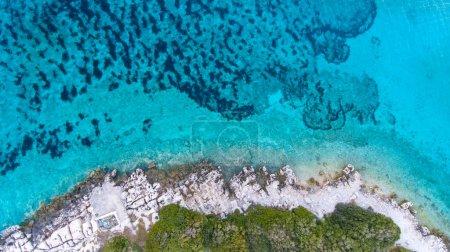 Photo pour Vue de clair, de dessus l'eau bleue turquoise et côte rocheuse - image libre de droit