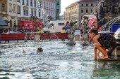 Olomouc, Česká republika - Kristýna 25, 2016: horký letní den děti hrají v bazénu fontána u Staroměstského náměstí