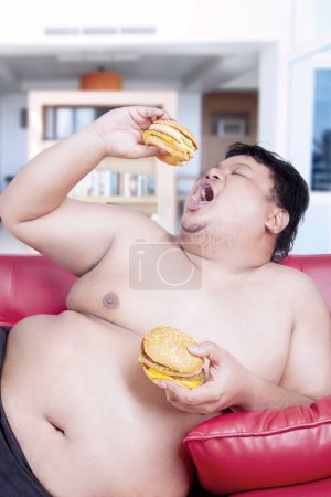 Fat man eating burgers on the sofa