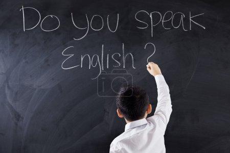 Photo pour Élève du primaire mâle écrit le texte de faire vous parler anglais sur le tableau noir - image libre de droit