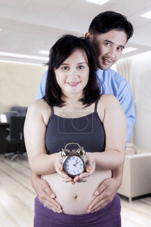 Husband holds pregnant tummy with clock