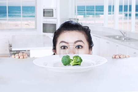 Fat woman peeping broccoli
