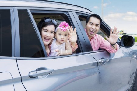 Cheerful family waving hands in the car