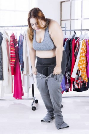 Overweight woman with old jeans at home