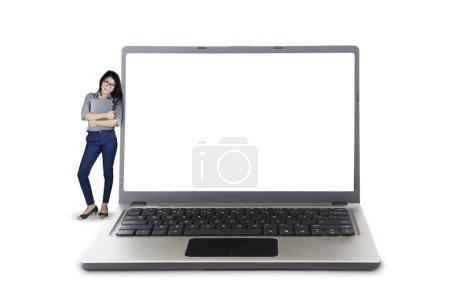 Businesswoman leaning on big laptop