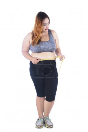 Fat woman measures her belly on studio