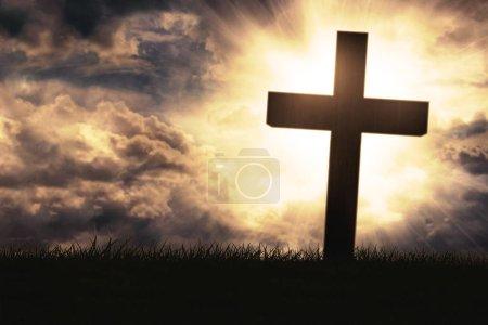 Silhouette of cross symbol on grass