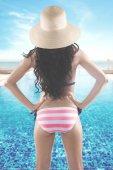 Back view of woman in bikini at pool