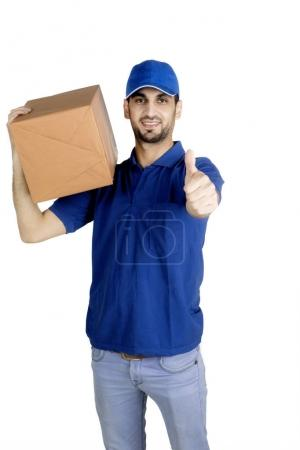 Delivery man showing thumb up on studio