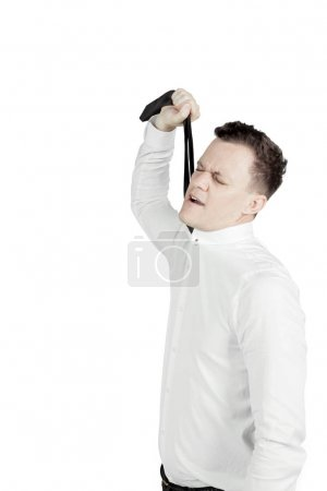 Caucasian businessman strangling his neck on studio