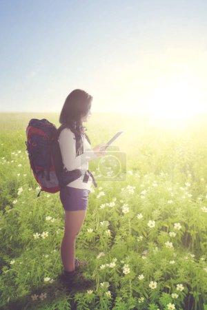 Photo pour Portrait de jeune touriste utilisant une tablette numérique tout en se tenant debout sur la prairie de fleurs - image libre de droit