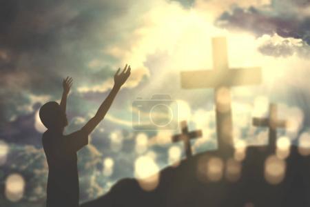 Photo pour Portrait d'un jeune homme ouvrant les bras tout en louant et en priant Dieu avec trois crucifix au lever du soleil - image libre de droit