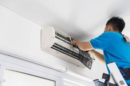 Photo pour Image d'un technicien masculin inconnu réparant un climatiseur à la maison - image libre de droit